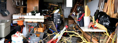 A very cluttered garage in need of a clearance.